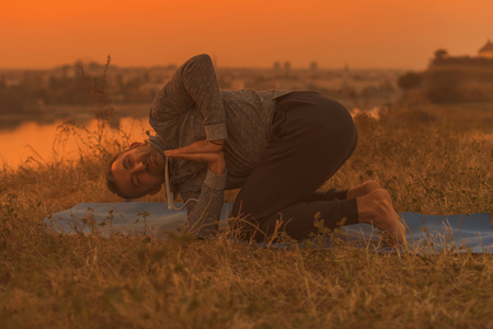 Man doing yoga on sunset with city view,variation of Revolved Chair Pose  Parivrtta Utkatasana Toned image. Stock Photo