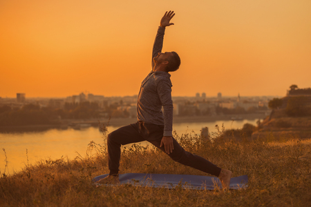 Man doing yoga on sunset with city view, Warrior 1 PoseVirabhadrasana I. Toned image.