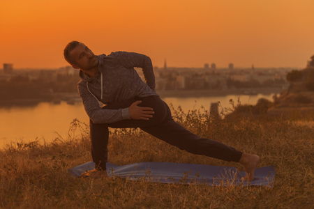 Man doing yoga on sunset with city view, variation of Noose Pose Pasasana Toned image.