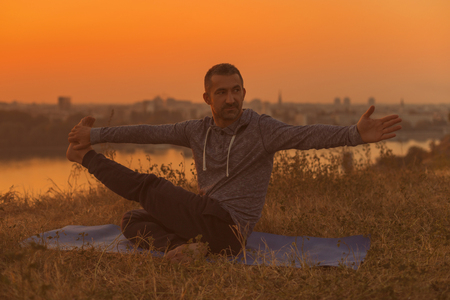 Man doing yoga on sunset with city view variation of Boat poseNavasana , Toned image.
