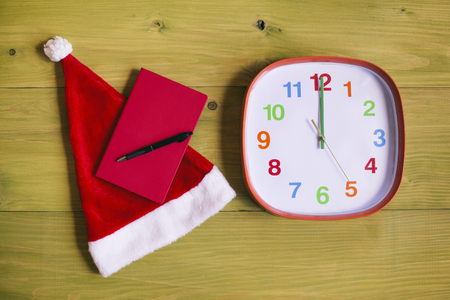 Image of Santa Hat,personal organizer and clock showing midnight wooden table.Toned image. Imagens