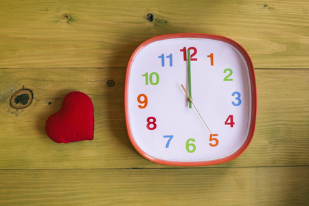 Image of clock showing midnight and heart on wooden table.Toned image. Imagens