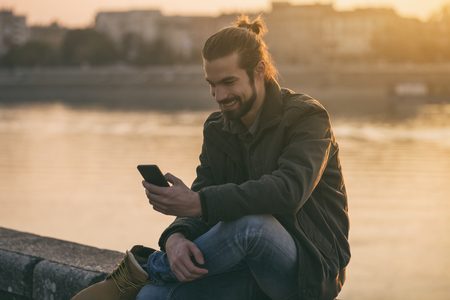 Handsome modern businessman using phone while sitting by the river.Toned image. Stok Fotoğraf