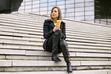 Beautiful businesswoman enjoys resting outdoor at the city and drinking coffee.Toned image.