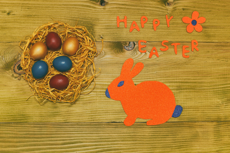 Happy Easter message with painted eggs in straw,bunny and flower on wooden table.Toned photo. Stock Photo