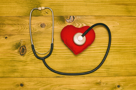 Image of fruit,stethoscope and heart shape on wooden table.Toned photo.