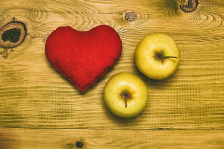 Image of apples with heart shape on wooden table.Toned photo.