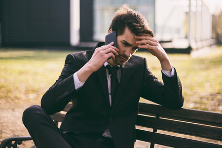 Worried businessman using phone while sitting outdoor.Toned image.