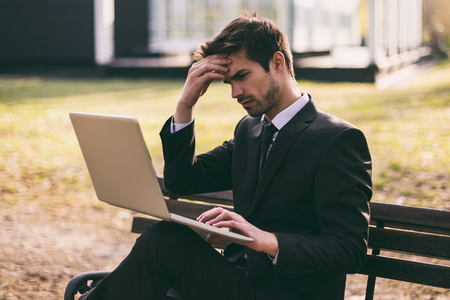 Worried businessman using laptop while sitting outdoor.Toned image.