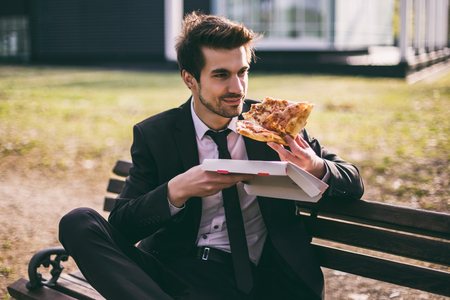 Elegant businessman enjoys eating pizza on his lunch break while sitting outdoor.Toned image.