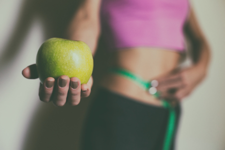 Fit woman measuring her tin waist  with a tape measure and showing apple.Focus on apple.Weight loss concept. Stock Photo