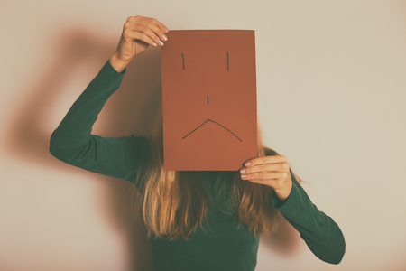 Depressed woman with sad face on paper standing alone in front of wall.Toned image. Reklamní fotografie