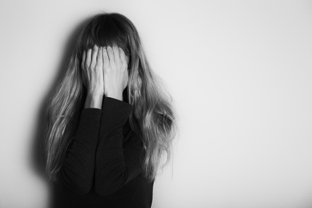 Depressed woman standing alone in front of wall.Intentionally black and white image. Reklamní fotografie
