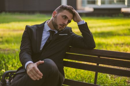 Worried businessman sitting outdoor.Toned image.
