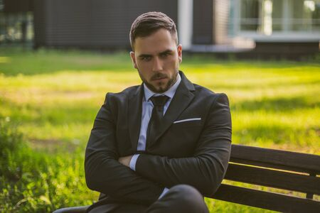 Angry businessman sitting outdoor.Toned image. 写真素材
