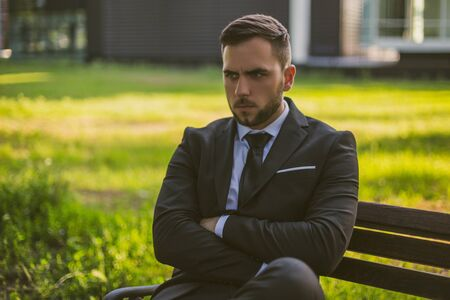 Angry businessman sitting outdoor.Toned image.