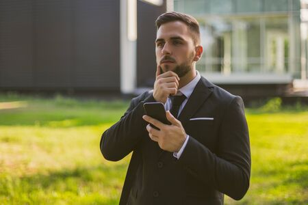 Worried businessman using phone while standing outdoor.Toned image.