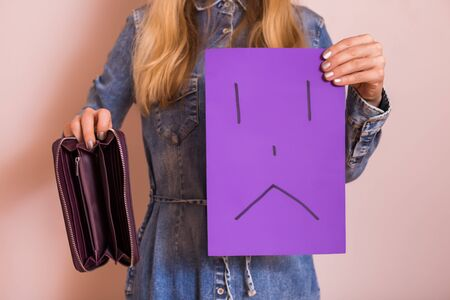 Woman holding empty wallet and sad face on paper while standing in front of wall.
