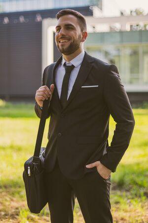 Portrait of elegant businessman enjoys standing outdoor.Toned photo.