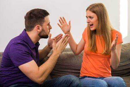 Angry wife and husband are having conflict while they sitting on sofa at their home.