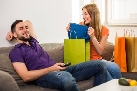 Wife is showing to her husband her new t-shirt,but husband is not interested and watching tv. Stock fotó