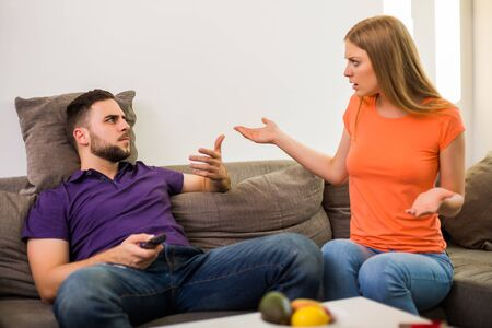 Angry wife and husband are having conflict because husband is watching tv too much.