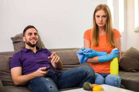 Angry wife and husband are having conflict because husband is never helping his wife with cleaning house.
