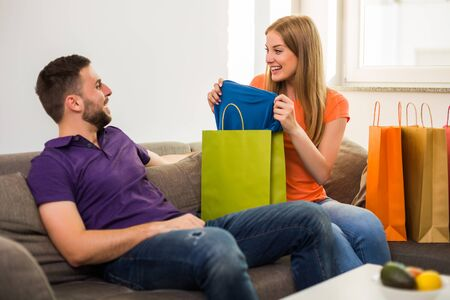 Wife is showing to her husband her new t-shirt and shopping bags while they sitting at their home.