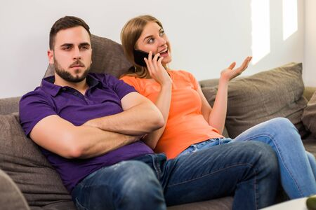 Angry wife and husband are having conflict because wife is using phone too much. Stock fotó