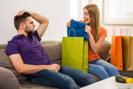 Couple having conflict because wife spent too much money on shopping while they sitting at sofa in their home.
