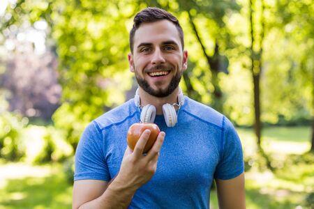 Sportieve man die appel eet in het park.