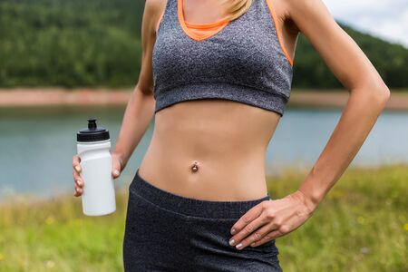 Close up stomach of a sporty woman with abs and bottle of water in the beautiful nature.