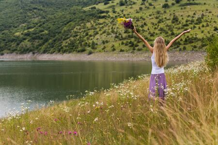 Woman with her arms outstretched enjoys in the nature and holding bouquet of flowers.