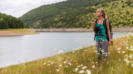 Woman hiker enjoys smelling flower while standing in the beautiful nature. 写真素材