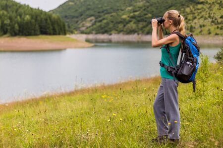 Woman hiker using binoculars while spending time in the beautiful nature
