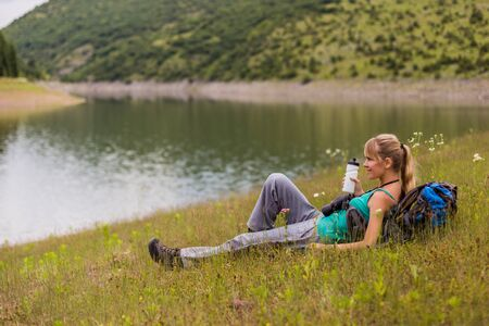 Woman hiker drinking water while spending time in the nature.