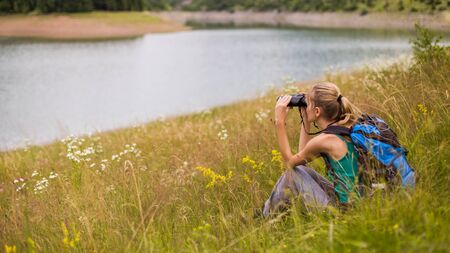 Woman hiker using binoculars while spending time in the beautiful nature.