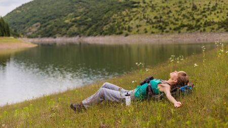 Woman hiker enjoys resting in the beautiful nature.
