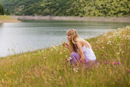 Woman smelling flowers while spending time in the beautiful nature. 写真素材