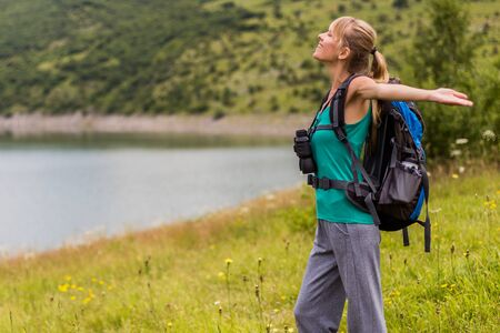 Woman hiker with arms raised enjoys in beautiful view in the nature.