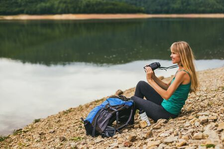 Woman hiker using binoculars while sitting by the lake. 写真素材