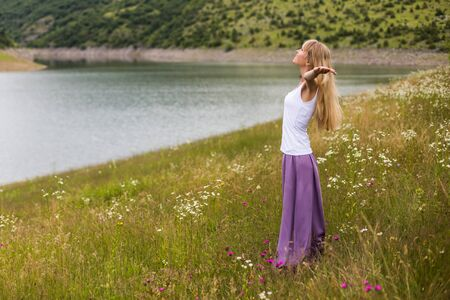 Woman with her arms outstretched enjoys spending her time in beautiful nature.