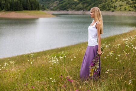 Woman holding bouquet of flowers and enjoys in the beautiful nature.