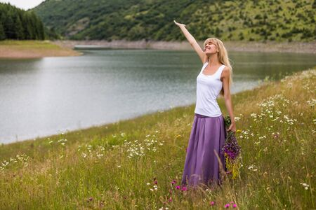 Woman with her arm raised enjoys in the nature and holding bouquet of flowers.