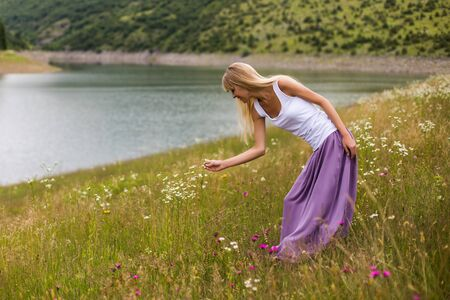 Woman picking flowers while enjoys spending time in the beautiful nature. 写真素材