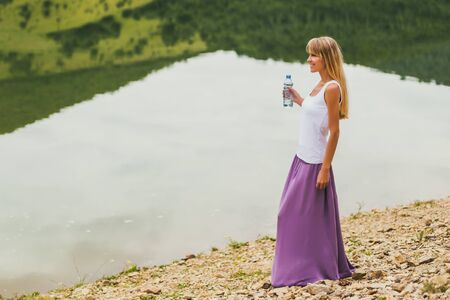 Woman enjoys drinking water while spending time by the lake.