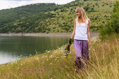 Woman holding bouquet of flowers and walking in the beautiful nature.