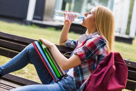 Female student drinking water while sitting outdoor.