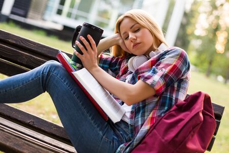 Tired female student fall asleep while  drinking coffee and studying outdoor.