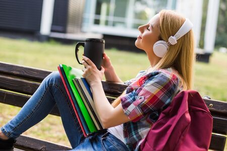 Female student with headphones enjoys listening music and drinking coffee outdoor.